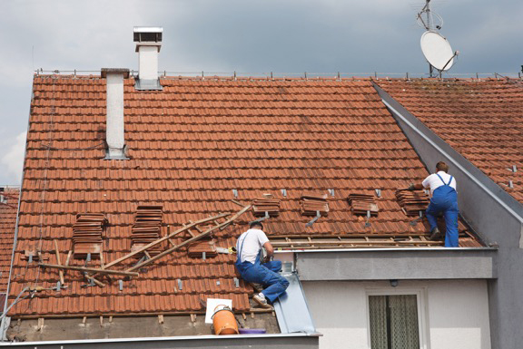 Roofers attaching shingles to a house